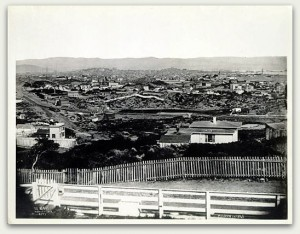 "View of the Mission in 1865, described as, ""Looking E. from Reservoir Hill, Market & Buchanan Sts., Vicinity Market & Valencia."" The ""rolling ..."" described by Palou are absent, with the only tree visible in the scene located near the fence in the lower left. Courtesy of the San Francisco Historical Photograph Collection, San Francisco Public Library."